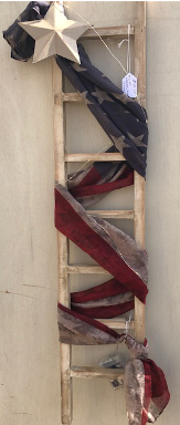 White wooden ladder with american flag banner and lights wrapped around it