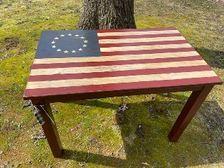 Wooden table with top painted in as a flag with 13 stars