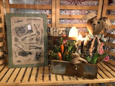 Green sign board with antique garden tools on aged paper, wood box with filled with carrots, a primitive bunny, electric candle, and flowers