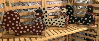 three wooden chickens in barn red with ivory polka dots, ivory with black polka dots, and black with ivory polka dots