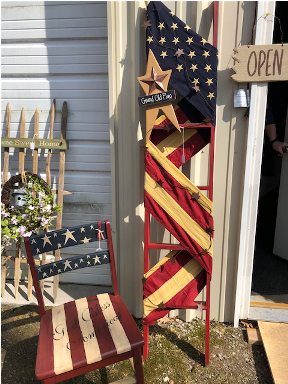 Wooden ladder with flag wrapped around it and star on top. Wood chair painted in Americana theme.